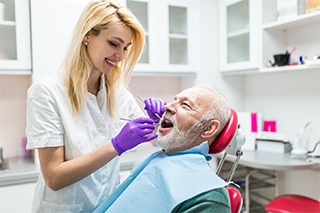 Implant dentist in Fort Worth examining a patient's mouth