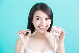 Woman holding Invisalign tray and model smile with braces