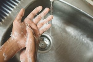 dentist following safety procedures by washing hands