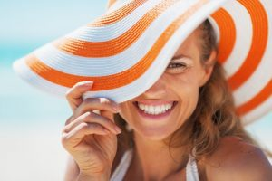 Woman in sun hat smiles after visiting Forth Worth cosmetic dentist